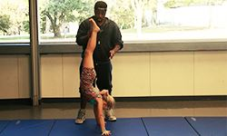 Instructor teaching a student a handstand
