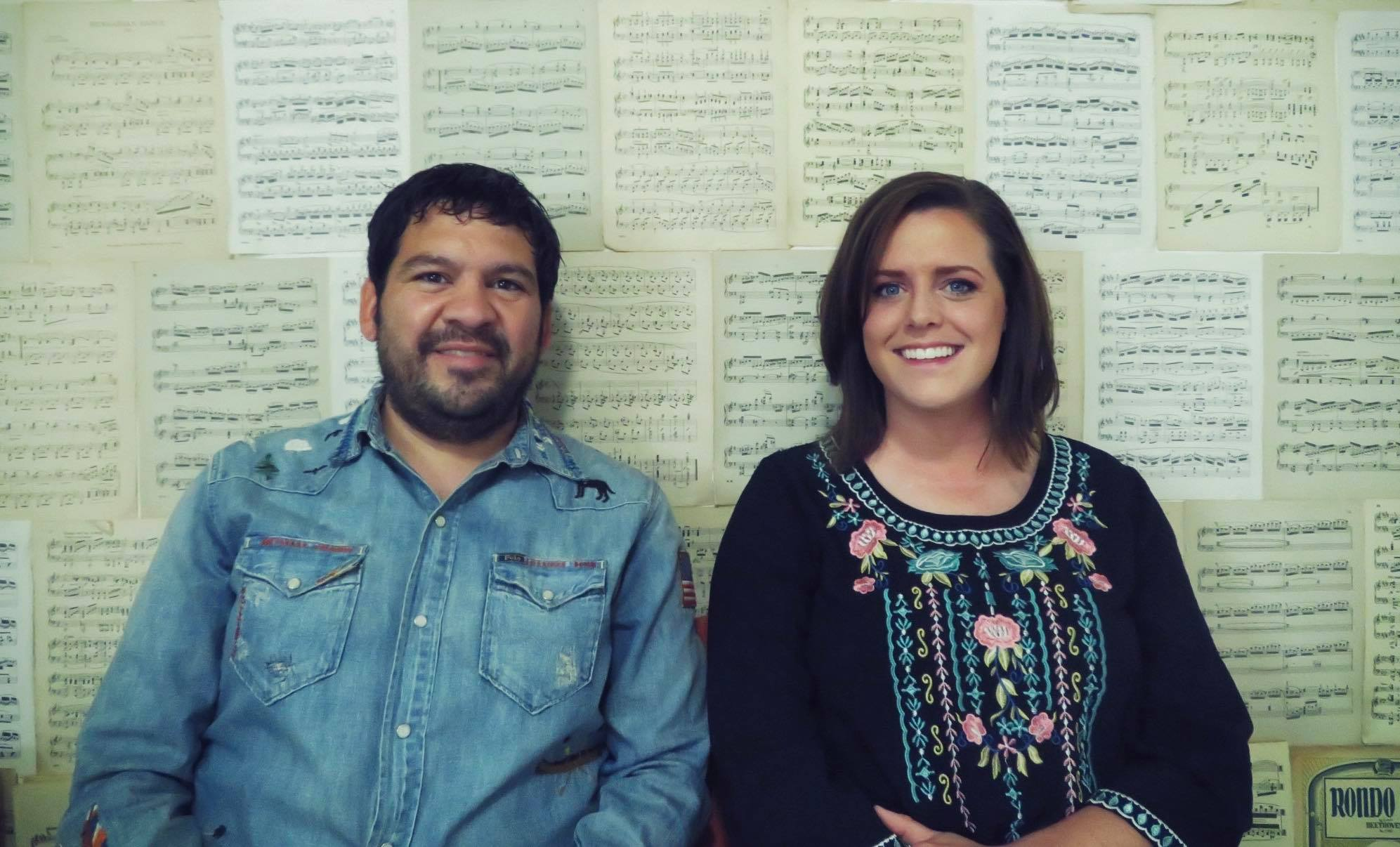 Bobby and his wife sitting in front of a wall covered with sheet music