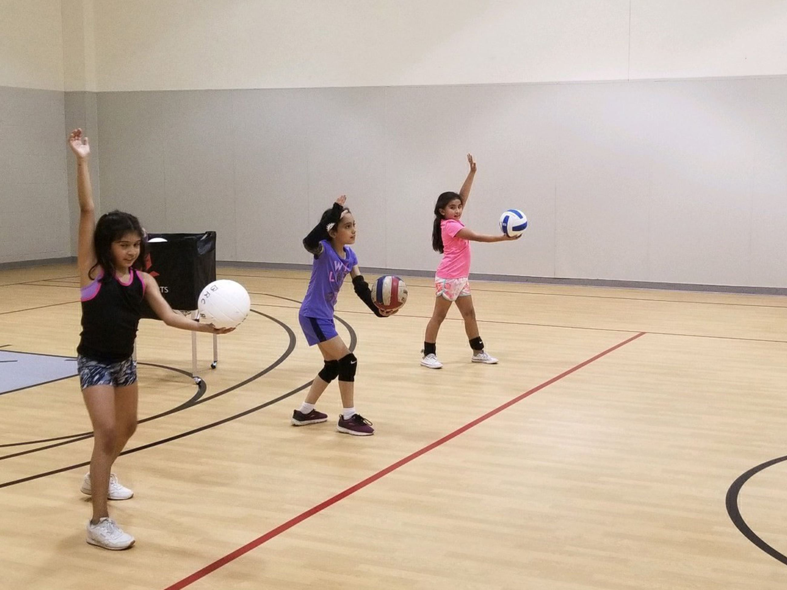 Kids playing volleyball in a gymnasium