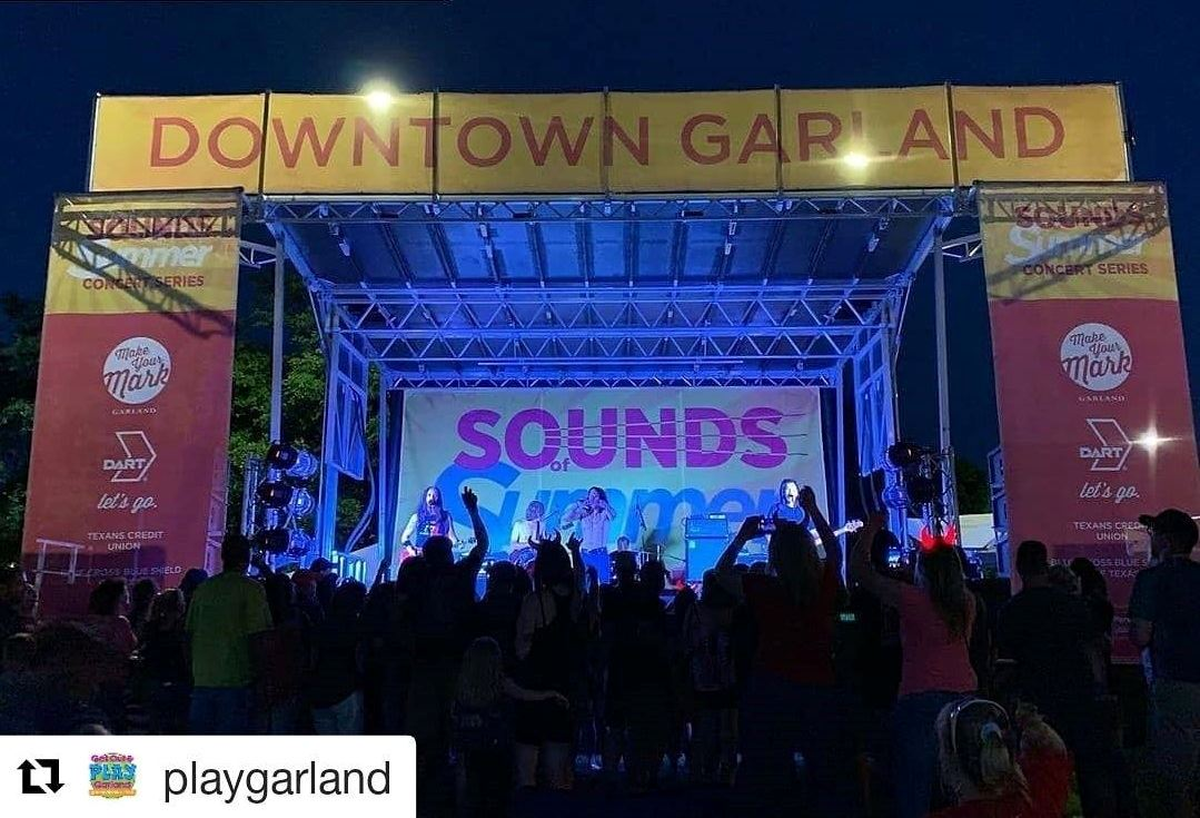 Concert Stage in the Square with banners and band playing on stage.